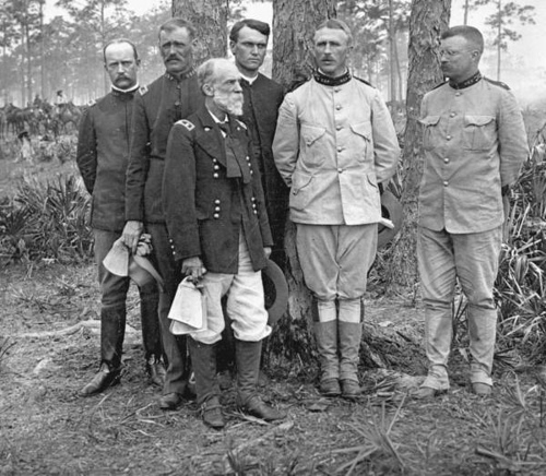 "De izquierda a derecha: Mayor George Dunn, Mayor Alexander Brodie, Mayor General Joseph Wheeler,  Capellán Henry A. Brown,  Coronel Leonard Wood, y Coronel Theodore ""Teddy"" Roosevelt. (later 26th U.S. President)."