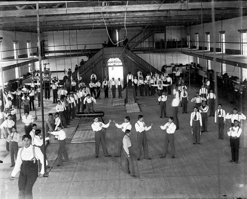 Carlisle_Students_in_School_Uniform_Exercising_Inside_Gymnasium;_Some_with_Indian_Clubs,_Others_with_Gymnastic_Equipment;_Non-Native_Group_Watching_1879
