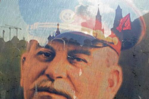 Russian Communists and their supporters are seen through a transparent portrait of Soviet dictator Josef Stalin as they lay flowers at his tomb at the Red Square in Moscow on March 5, 2013, to mark the 60th anniversary of Stalin's death. Photo by KIRILL KUDRYAVTSEV/AFP/Getty Images